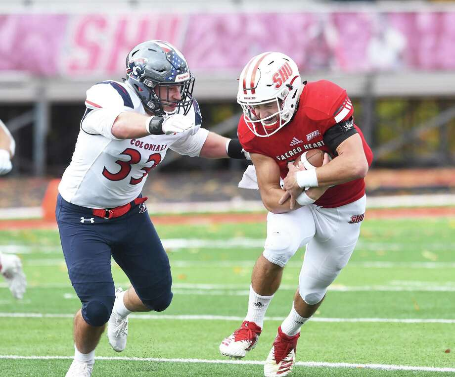 Sacred Heart quarterback Kevin Duke, right, looks to avoid a tackle from Robert Morris' Adam Wollet on Saturday in Fairfield. Photo: Krista Benson / For Hearst Connecticut Media / The News-Times Freelance