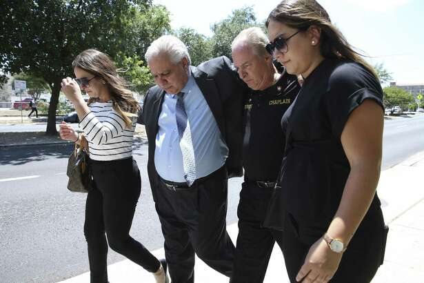 Gary Cain, second from left, is accompanied by friends and family as he walks out of the John H. Wood, Jr. U.S. Courthouse after sentencing for felony counts on June 27.