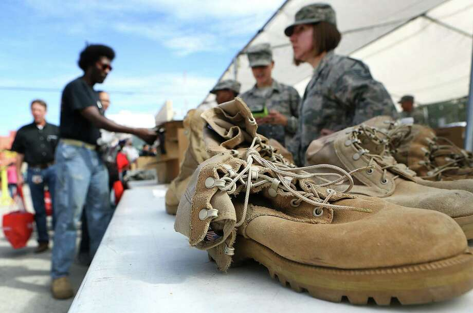 Military personel help hand out clothing items, including boots, at the 2014 Stand Down. Participants received haircuts, medical/dental screenings, flu shots, HIV tests, legal aid, clothing including military items, VA benefits and food. Legal aid remains a special need. Photo: BOB OWEN /San Antonio Express-News / © 2014 San Antonio Express-News