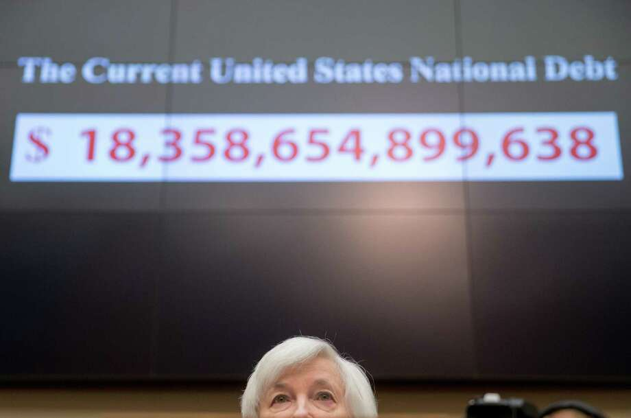 A screen depicting the real-time national debt of the United States as of December 2015 is displayed behind Federal Reserve Chair Janet Yellen as she testifies on Capitol Hill in Washington, during a hearing on banking supervision and regulation. The debt in October was $21.6 trillion. Photo: Andrew Harnik /Associated Press / AP