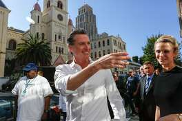 Gov. elect Gavin Newsom waves at supporters as he and wife Jennifer Siebel Newsom walk to St. Anthony's Dining Room to help serve lunch service on Thursday, November 8, 2018 in San Francisco, Calif.