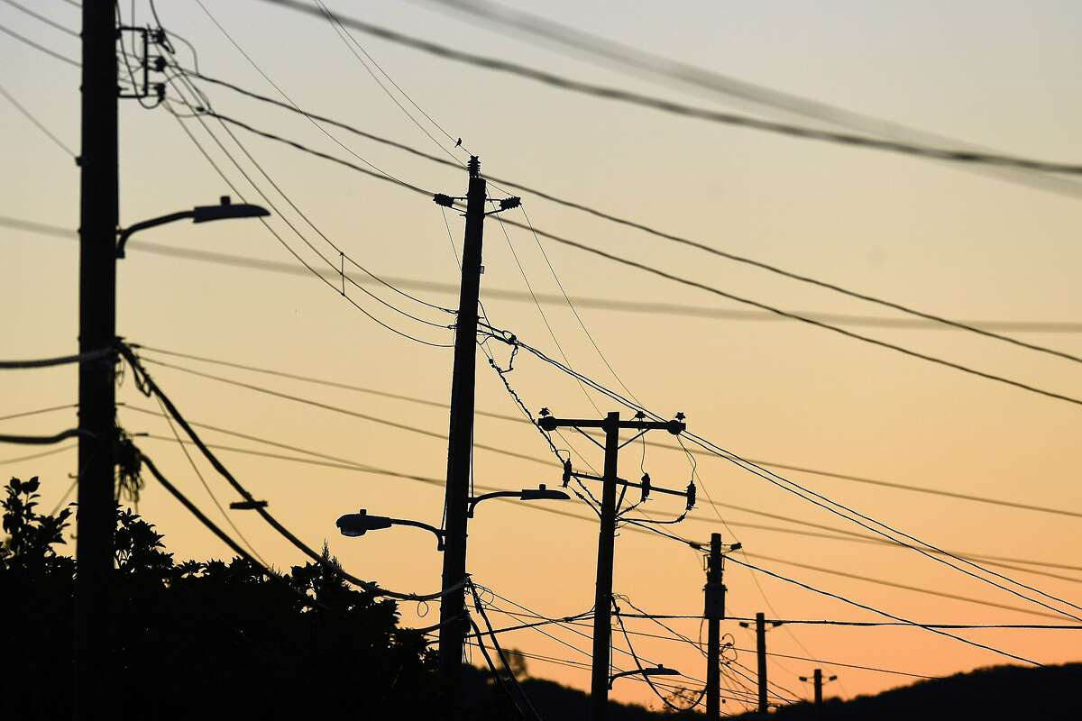 Power transmission lines cross a street in Sonoma, Calif., on Monday, Oct. 15, 2018. Some customers in the region remain without power after PG&E cut electric service in hopes of preventing fires amid red flag fire warnings.