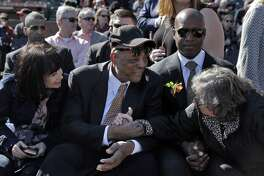 Deb Perry, wife of Gaylord Perry, right, reaches over to shake hands with Willie Mays during a public remembrance for Willie McCovey at AT&T Park in San Francisco, Calif., on Thursday, November 8, 2018.