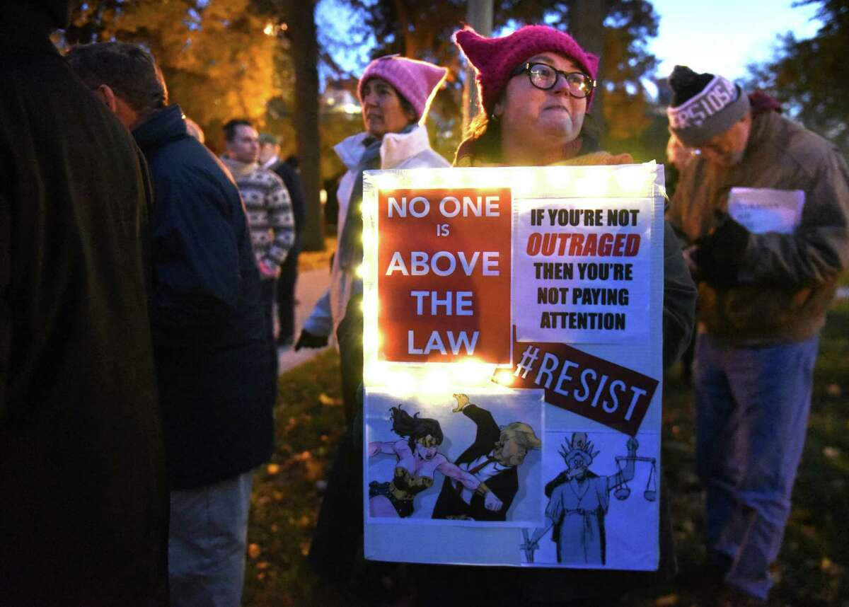 Becca Damour of Albany holds a sign aa people protest in Lafayette Park against the possibility of Trump and his acting Attorney General Matthew Whitaker firing Robert Mueller on Thursday, Nov. 8, 2018 in Albany, N.Y. (Lori Van Buren/Times Union)
