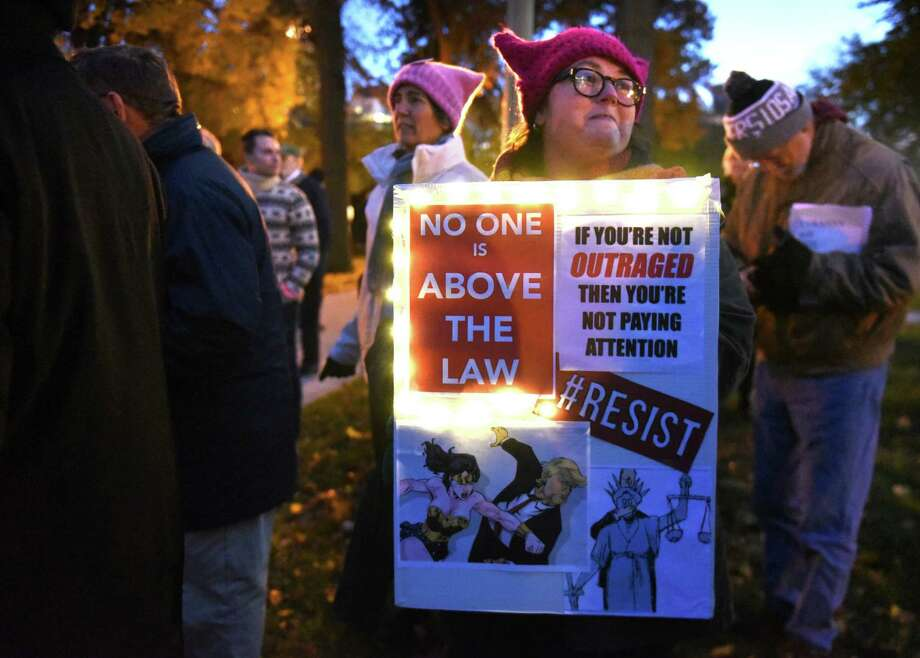 Becca Damour of Albany holds a sign aa people protest in Lafayette Park against the possibility of Trump and his acting Attorney General Matthew Whitaker firing Robert Mueller on Thursday, Nov. 8, 2018 in Albany, N.Y. (Lori Van Buren/Times Union) Photo: Lori Van Buren, Albany Times Union / 20045429A