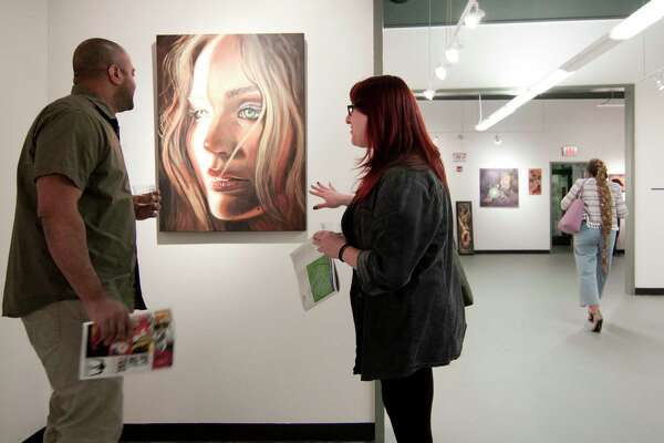 Cristyn Martino, of Black Rock, and her friend Sebastian Morrell, of Newtown, check out a piece of artwork by Liz Squillace during the 10th Annual Bridgeport Art Trail Downtown Kick-off and Artists' Party at Read's ArtSpace in Bridgeport, Conn. on Thursday Nov. 8, 2018. The exhibit's opening reception features new artwork from the Read's community, as well as work chosen by fellow Read's artists. The annual art festival runs until Nov. 11 and is a showcase for the city's thriving art and culture scene.