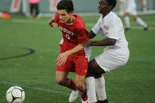 Fairfield Prep's Axel Whamond is held by East Hartford's Garvans Pamphile during their second round game in the Class LL boys soccer playoffs at Fairfield University in Fairfield, Conn. on Thursday, October 8, 2018.