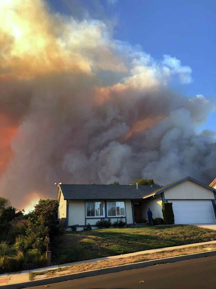 Plumes of smoke loom in the sky several miles away, seen behind a home in Thousand Oaks, Calif., as a wind-driven wildfire known as the Hill fire threatens the area late Thursday afternoon, Nov. 4, 2018. This is a few miles from the scene of Wednesday's mass shooting at the Borderline Bar in Thousand Oaks. Photo: Kathleen Ronayne, AP / Copyright 2018 The Associated Press. All rights reserved.