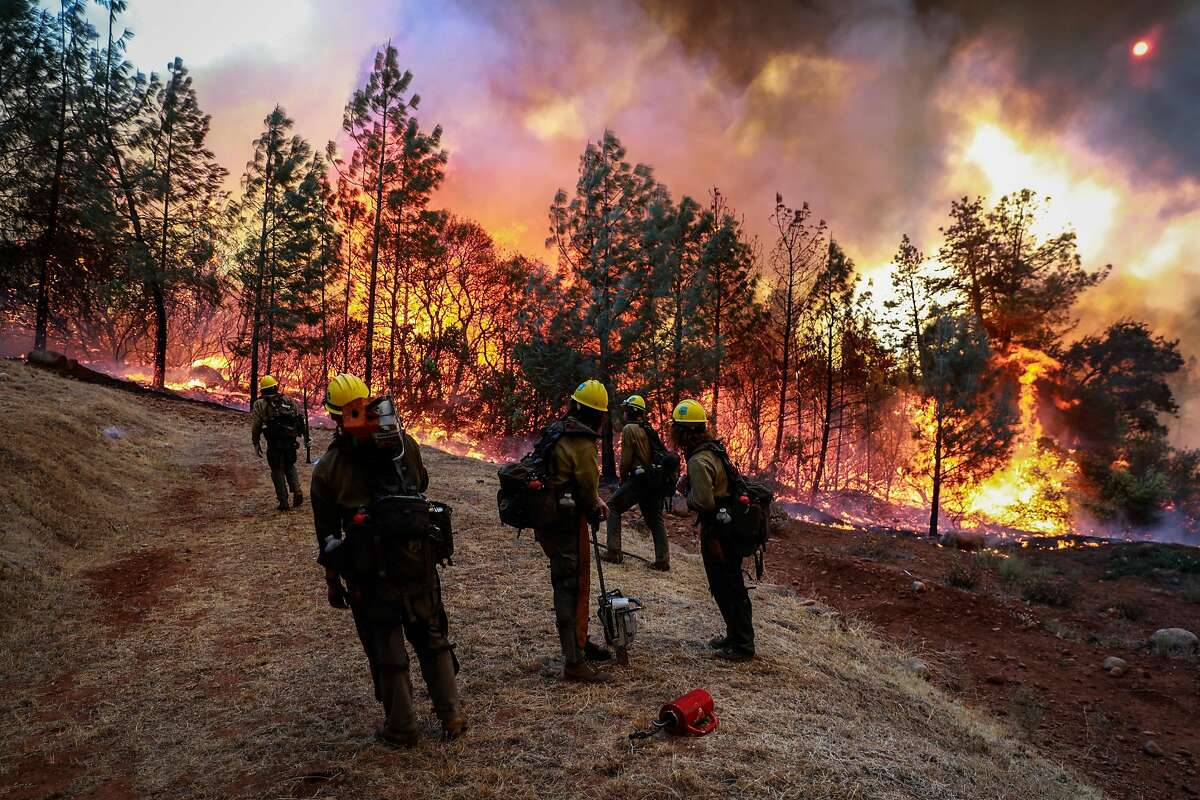 A group of hotshots watch as the Camp Fire burns off of Pentz Road in Paradise, California, on Thursday, Nov. 8, 2018.