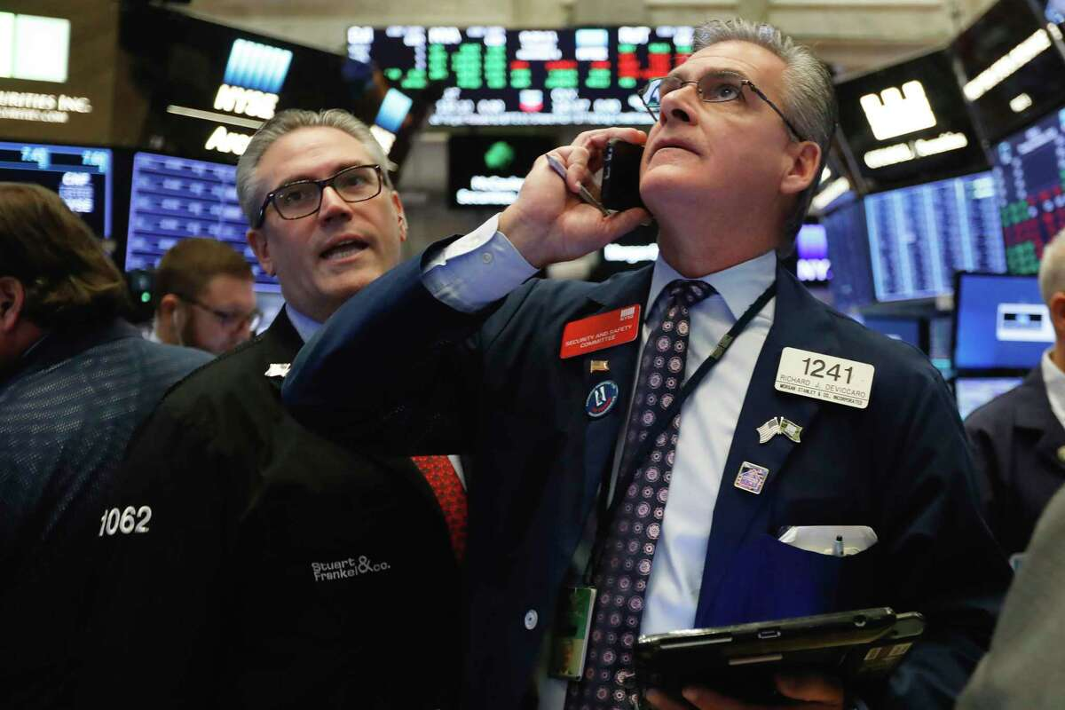 Traders Eric Schumacher, left, and Richard Deviccaro work on the floor of the New York Stock Exchange, Thursday, Nov. 8, 2018. Stocks are opening modestly lower on Wall Street as the market gives back some of its big gains from the day before. (AP Photo/Richard Drew)