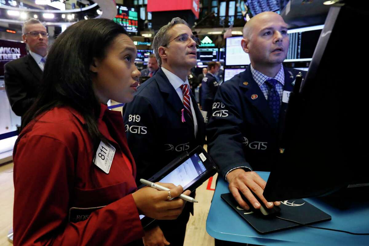Trader Lauren Simmons, left, woks with specialists Lauren Simmons on the floor of the New York Stock Exchange, Thursday, Nov. 8, 2018. Stocks are opening modestly lower on Wall Street as the market gives back some of its big gains from the day before. (AP Photo/Richard Drew)