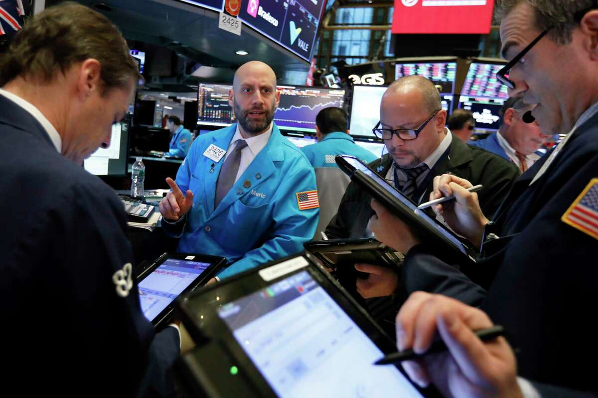 Specialists Meric Greenbaum, second left, works with traders at his post on the floor of the New York Stock Exchange, Thursday, Nov. 8, 2018. Stocks are opening modestly lower on Wall Street as the market gives back some of its big gains from the day before. (AP Photo/Richard Drew)