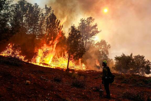 A hotshot firefighter watches as the Camp Fire burns off of Pentz Road in Paradise, California, on Thursday, Nov. 8, 2018.