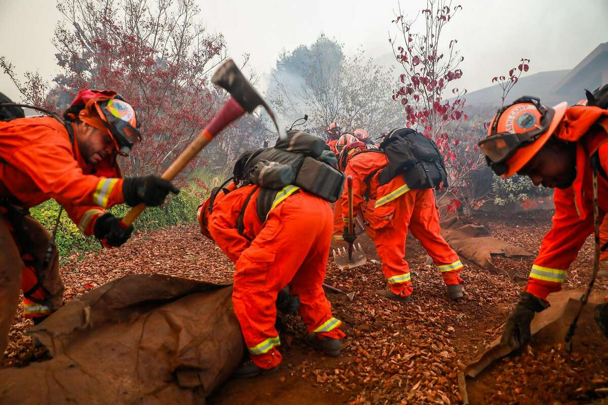 Inmate firefighters dig a trench to try and save a house off of Pentz Road during the Camp Fire in Paradise, California, on Thursday, Nov. 8, 2018.