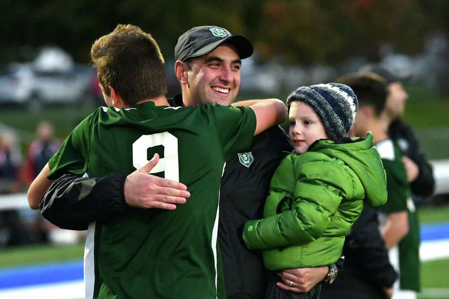 Schalmont's Gabe Comenzo, left, hugs head coach Vito Urbano after defeating Ichabod Crane in the Class B boys' soccer final in overtime on Monday, Oct. 29, 2018 in Troy, N.Y. (Lori Van Buren/Times Union) Photo: Lori Van Buren / 40045307A