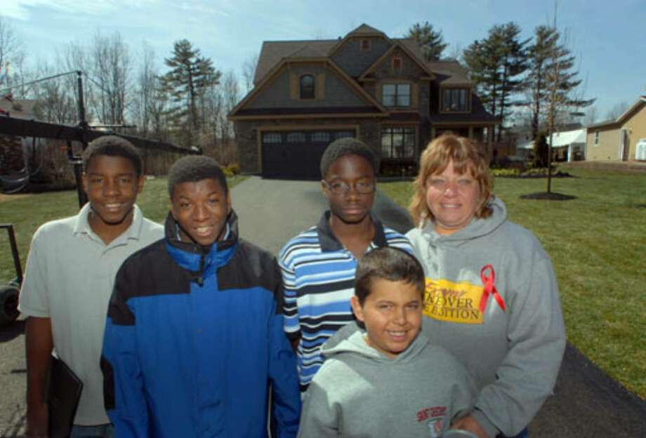 Debbie Oatman and her sons, from left, Brian, 15, D.J., 20, Kevin, 16, and Scout, 10, stand in front of their new home. Photo: Michael P. Farrell