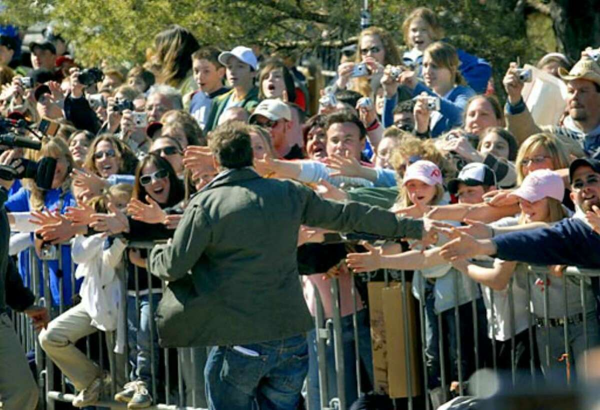 Ty Pennington slaps hands with spectators prior to the unveiling of the Oatman home.