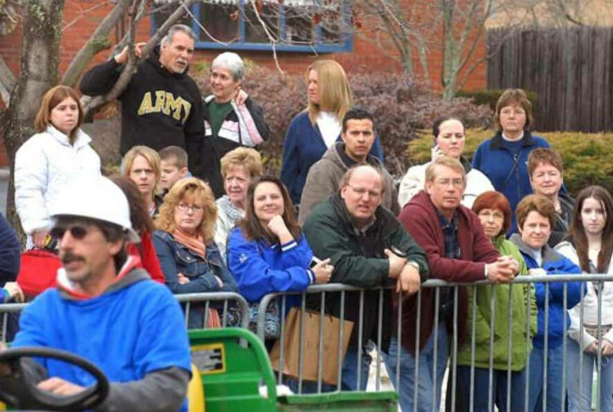 Spectators observe from a distance as workers continue construction at Debbie Oatman's home, Tuesday
