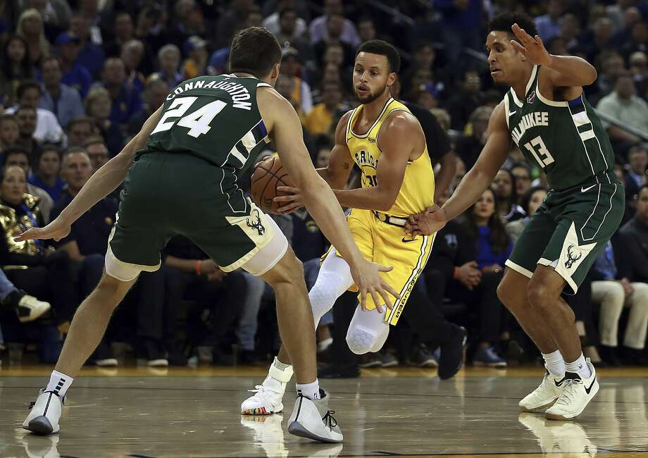 Golden State Warriors' Stephen Curry, center, drives the ball between Milwaukee Bucks' Pat Connaughton (24) and Malcolm Brogdon, right, during the first half of an NBA basketball game Thursday, Nov. 8, 2018, in Oakland, Calif. (AP Photo/Ben Margot) Photo: Ben Margot / Associated Press