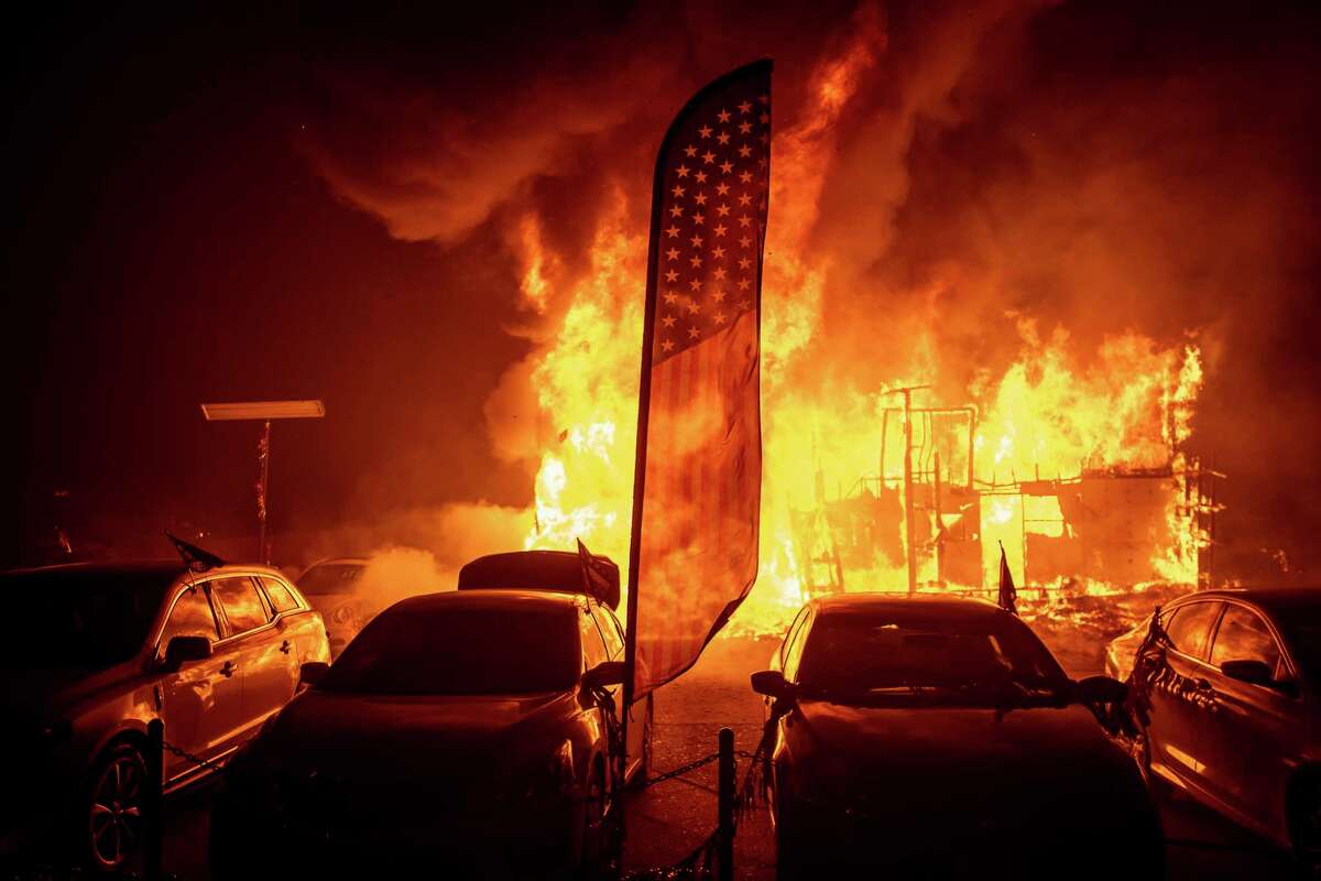 Flames consume a car dealership as the Camp Fire tears through Paradise, Calif., on Thursday, Nov. 8, 2018. Tens of thousands of people fled a fast-moving wildfire Thursday in Northern California, some clutching babies and pets as they abandoned vehicles and struck out on foot ahead of the flames that forced the evacuation of an entire town and destroyed hundreds of structures.