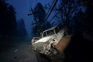 A scorched vehicle rests on a roadside as the Camp Fire tears through Paradise, Calif., on Thursday, Nov. 8, 2018. Tens of thousands of people fled a fast-moving wildfire Thursday in Northern California, some clutching babies and pets as they abandoned vehicles and struck out on foot ahead of the flames that forced the evacuation of an entire town and destroyed hundreds of structures.