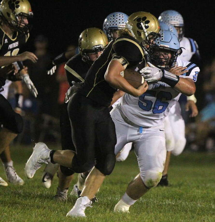 Triopia's Zach Rouland catches up with a Camp Point Central ball carrier during a high school football game earlier this season.