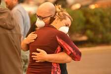 Two people embrace in the parking lot of the Feather River Hospital as it burns in Paradise, California on November 8, 2018. - Dozens of patients were quickly evacuated as impending flames engulfed the hospital. More than 18,000 acres have been scorched in a matter of hours burning with it a hospital, a gas station and dozens of homes. (Photo by Josh Edelson / AFP) (Photo credit should read JOSH EDELSON/AFP/Getty Images)