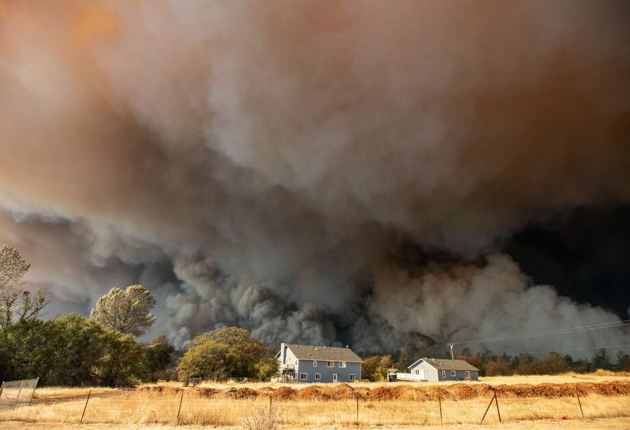 TOPSHOT - A home is overshadowed by towering smoke plumes as the Camp fire races through town in Paradise, California on November 8, 2018. - More than 18,000 acres have been scorched in a matter of hours burning with it a hospital, a gas station and dozens of homes. Photo: JOSH EDELSON/AFP/Getty Images