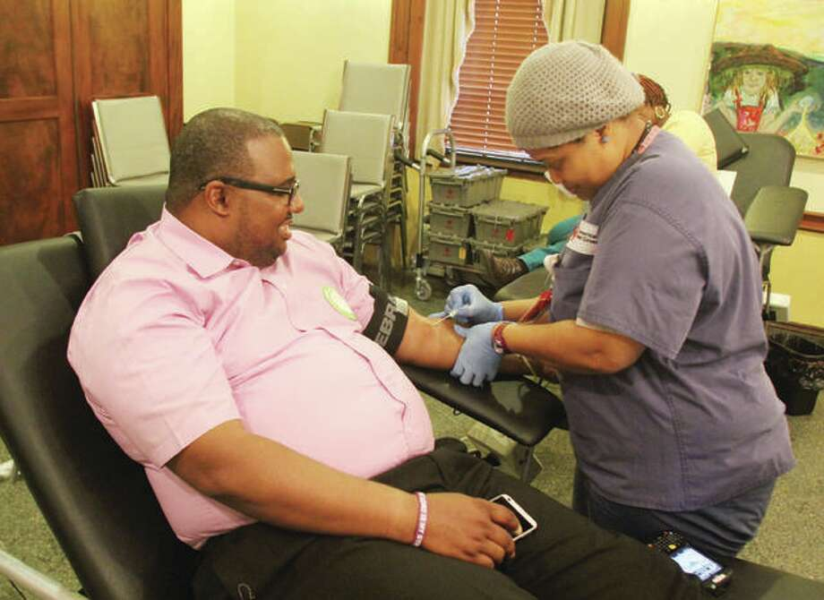 Steed Cross, of Alton, gives blood with the help of Red Cross collection specialist Shalvona Dickens, during the A Precious Organization Holiday Sickle Cellebration in 2015. Photo: Scott Cousins | The Telegraph