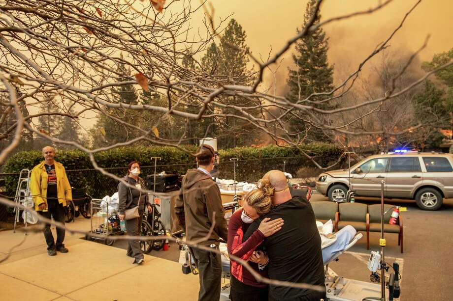 Nurse Cassie Lerossignol hugs as coworker as the Feather River Hospital burns while the Camp Fire rages through Paradise, Calif., on Thursday, Nov. 8, 2018. Tens of thousands of people fled a fast-moving wildfire Thursday in Northern California, some clutching babies and pets as they abandoned vehicles and struck out on foot ahead of the flames that forced the evacuation of an entire town. With California fire season well underway, it's clear that people and pets will need help in the days, weeks and months to come. People interested in volunteering or donating as-needed may sign up with the Red Cross. The Red Cross has a volunteer page here. Photo: Noah Berger, AP / Noah Berger