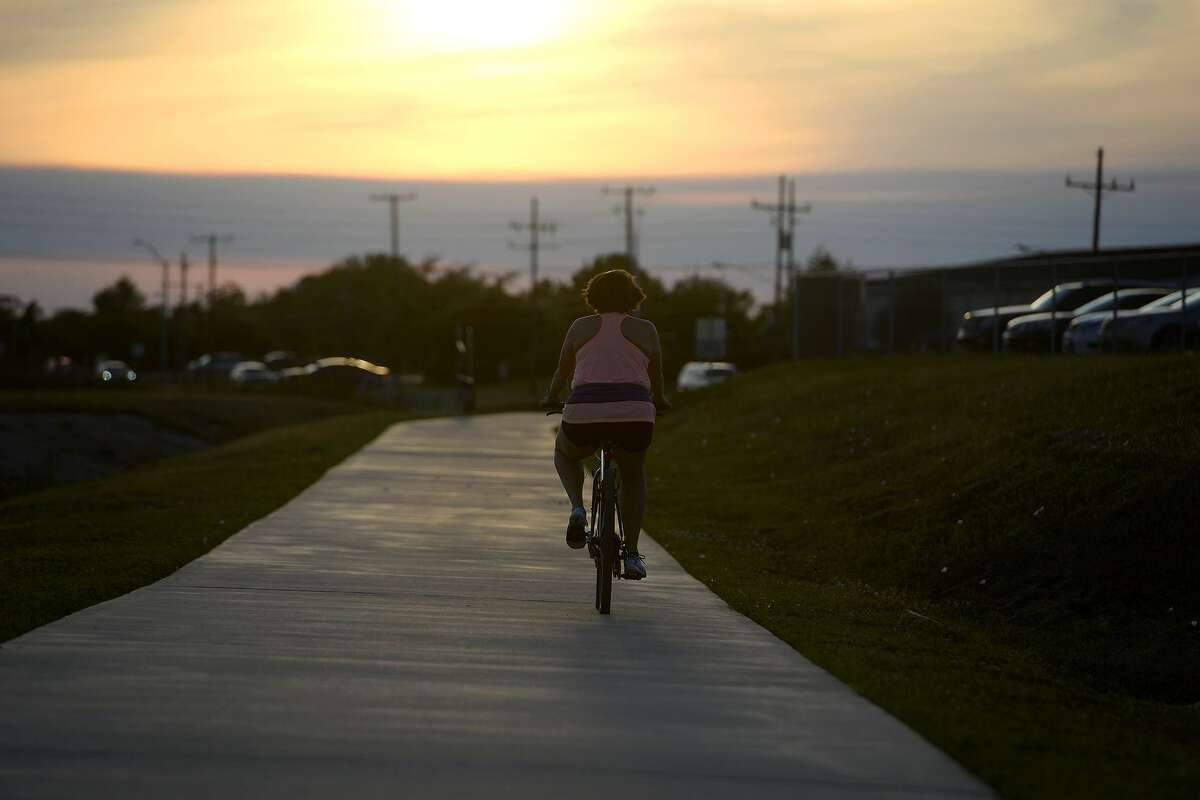 A cyclist rides toward the setting sun at the Folsom Hike and Bike Trail. Darin Lopez has started a petition to have the city put lights on the trail so people can use it after work during the winter, when the sun sets early. Photo taken Friday 4/27/18 Ryan Pelham/The Enterprise>>>See for some of the best bike and hike trails in Houston...