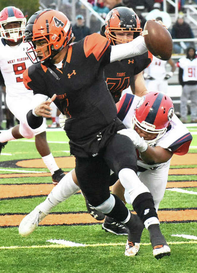 Edwardsville QB Kendall Abdur-Rahman (front) tries to shake free from a West Aurora tackler in a Class 8A playoff game last Saturday in Edwardsville. Photo: Matt Kamp / Hearst Illinois