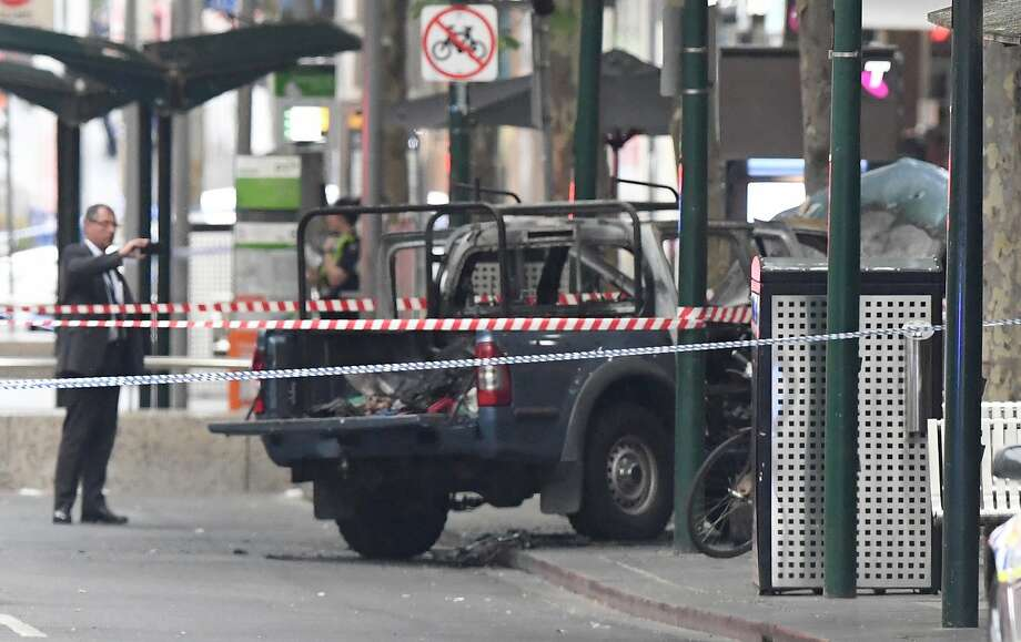 A burnt out vehicle belonged to a knife-wielding man, who stabbed three people, one fatally. Photo: James Ross / Associated Press