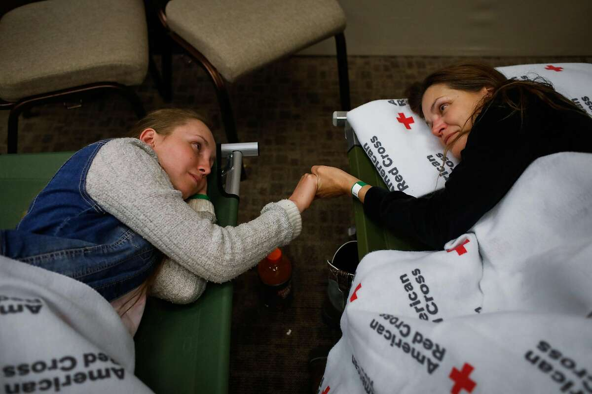 Evacuees Heidi Bigelow (right) and daughter Marina Joy Bigelow, 18 (left) who fled their home in Paradise, take a moment with each other at the Red Cross shelter in Chico, California, on Thursday, Nov. 8, 2018.
