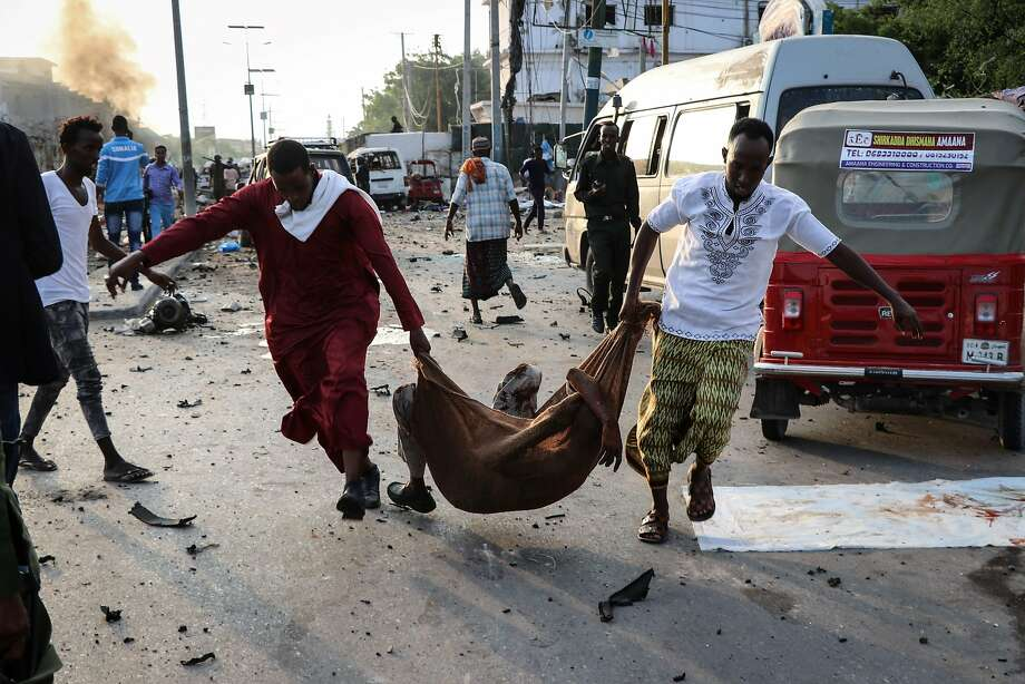 Two men rescue a wounded person following four suicide bomb car attacks in Somalia's capital of Mogadishu. The al Qaeda-linked al-Shabab rebel group claimed responsibility for the bombings. Photo: Abdirazak Hussein Farah / AFP / Getty Images