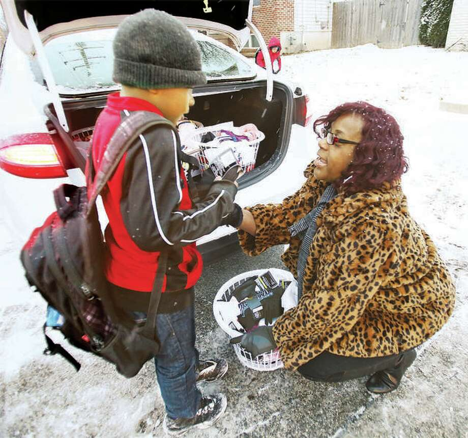 Rosetta Brown last year gives socks to a young boy who showed up at the bus stop at Central Avenue and Pearl Street without a coat, with outside temperatures at about 16 degrees and snowing. Brown gathered several baskets of 500 pairs of new socks during last year's drive, and is again taking donations for the third annual drive this year. Photo: John Badman | The Telegraph