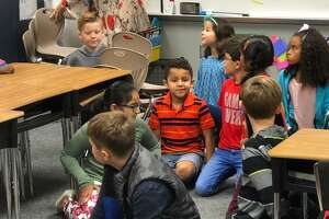 Christopher Morcos, 8, center with striped shirt, learns he is the 80,000th student in Katy ISD. A ceremony took place early Friday, Nov. 9, 2018, atDavidson Elementary School.