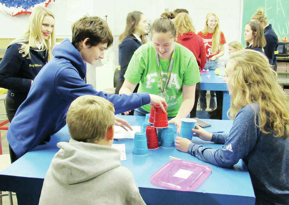 Alton High School students, from left, Gabe Hayes, Emily Carter (green shirt) and Sydney Stutz work together to build a safe, strong tower during an after-school FFA event. At far left is one of the FFA officers who conducted a chapter visit to the school. Photo: Charles Bolinger | The Telegraph