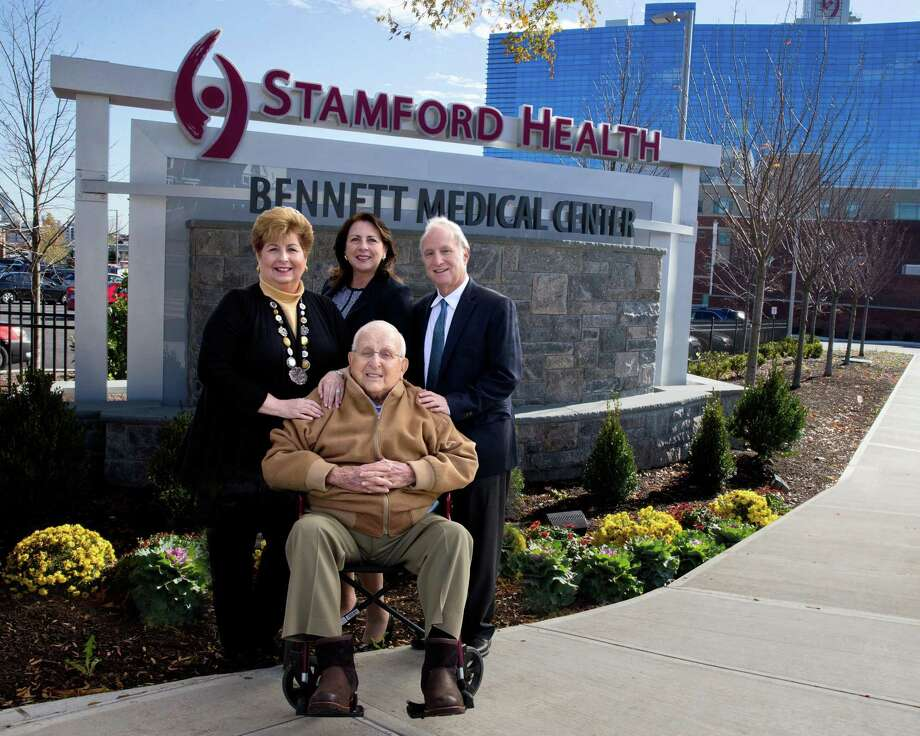 New signs have been installed at the main West Broad Street entrance to Stamford Hospital, whose campus is also known as the Bennett Medical Center. The Bennett family has given a total of more than $20 million to the hospital. In front center is Carl Bennett. In back, from left, are Robin Bennett-Kanarek, daughter of Carl Bennett; Kathy Silard, CEO of the Stamford Health system; and Marc Bennett, son of Carl Bennett. Photo: Contributed Photo