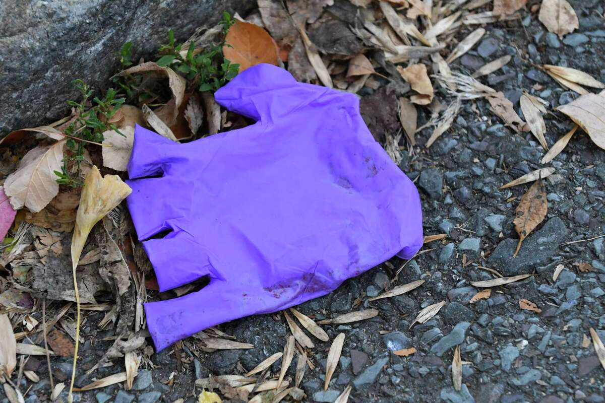 A blood stained exam glove is left at the scene of a shooting at Park Avenue and Philip Street where a 22-year-old man was shot on Friday, Nov. 9, 2018, in Albany N.Y. The incident occurred just before midnight Thursday, police said. He is in critical condition. (Will Waldron/Times Union)