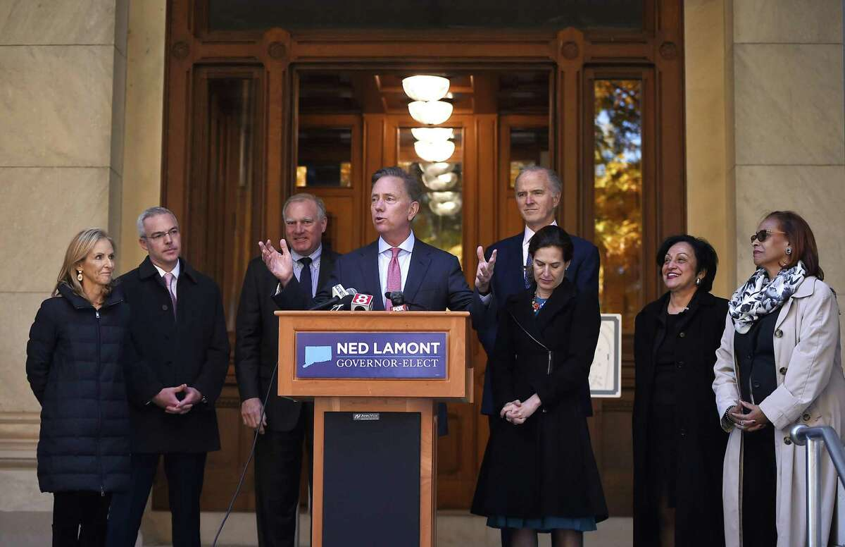 Connecticut's new governor-elect Ned Lamont introduces his transition team during a news conference at the State Capitol in Hartford, Conn., Thursday, Nov. 8, 2018. From the left is wife Annie Lamont and transition team members, Ryan Drajewicz, Connecticut Attorney General George Jepsen, Garrett Moran, incoming lieutenant governor Susan Bysiewicz, Dr. Elsa Nunez, and State Rep. Toni Walker.