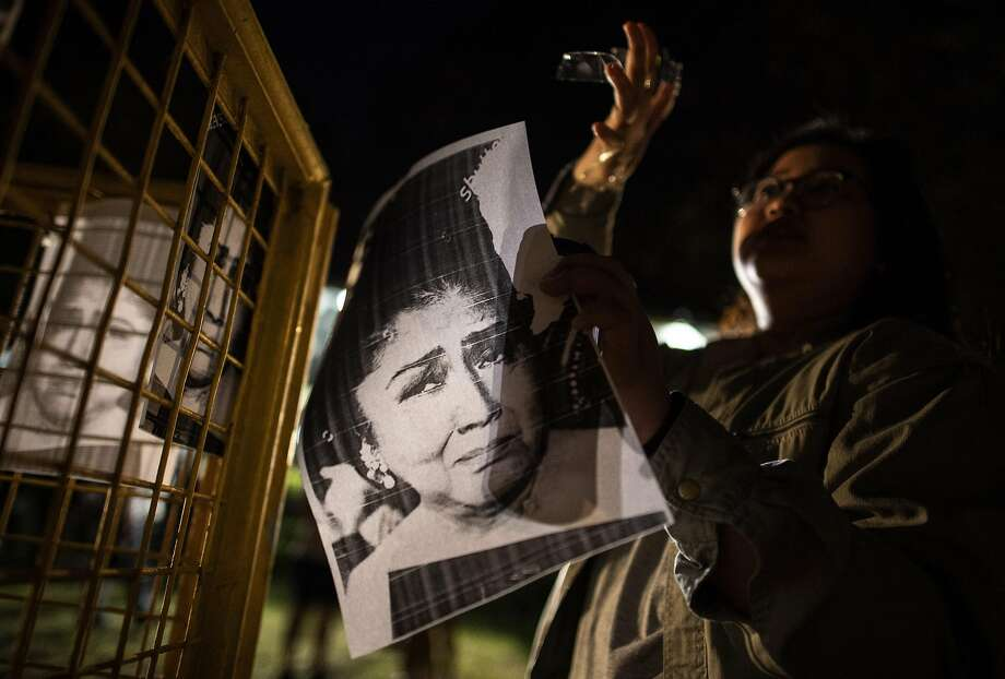 A protester holds a picture of the former first lady to mark her corruption conviction in Manila. Photo: NOEL CELIS;Noel Celis / AFP / Getty Images
