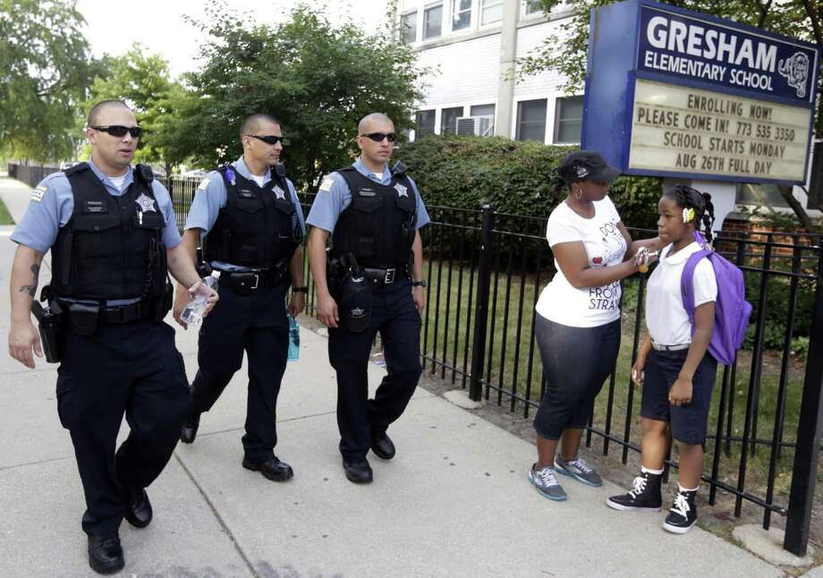 Chicago Police patrol the neighborhood as Crystal Stoval delivers her niece Kayla Porter from their south side home to Gresham Elementary School on the first day of classes in August 2013 in Chicago. Chicago Public Schools closed about 50 schools and programs that year. Photo: M. Spencer Green / Associated Press / AP