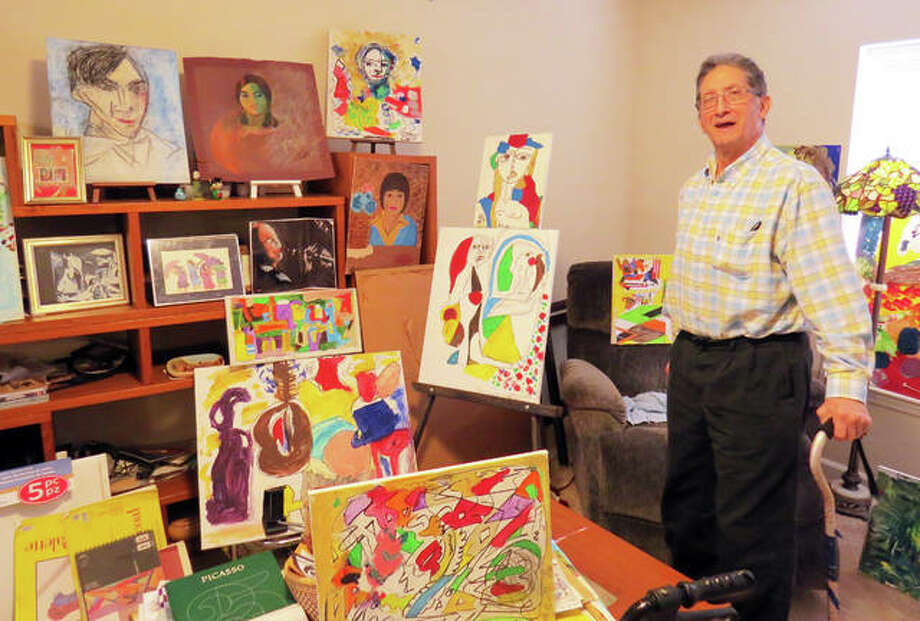 Dr. Paul Wanda stands proudly with several of his paintings in his apartment at Eden Village. Wanda took up the hobby after retiring from teaching Microbiology and biophysics at SIUE. Photo: Carol Arnett | The Intelligencer