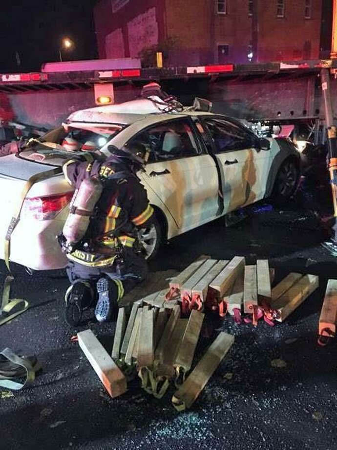 Bridgeport, Conn., firefighters freed someone trapped in their car under a tractor trailer's flatbed on Nov. 3, 2018. Photo: Contributed Photo / Bridgeport Fire Department / Contributed Photo / Connecticut Post Contributed