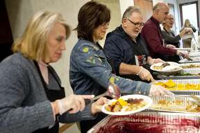 From left, Bonnie Otto, Midland County Administrator/Controller Bridgette Gransden, Midland County Commissioner Scott Noesen and Midland County District Court Judge Michael D. Carpenter serve lunch to people during the Project Community Connect event on Wednesday, Nov. 7, 2018 at Trinity Lutheran Church. (Katy Kildee/kkildee@mdn.net)