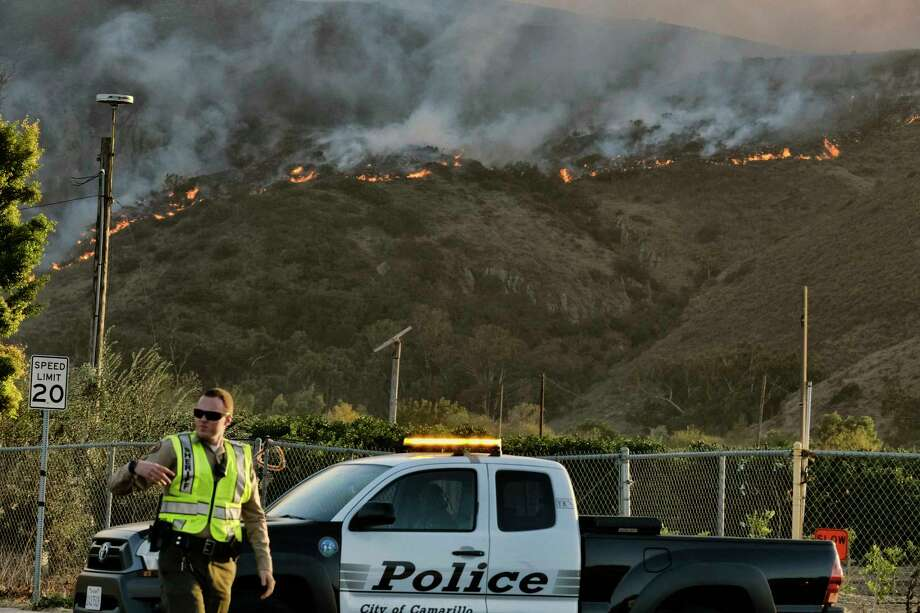 A police officer directs traffic at a checkpoint in front of an advancing wildfire Thursday, Nov. 8, 2018, near Newbury Park, Calif. The Ventura County Fire Department has also ordered evacuation of some communities in the path of the fire, which erupted a few miles from the site of Wednesday night's deadly mass shooting at a Thousand Oaks bar. Photo: Richard Vogel, AP / Copyright 2018 The Associated Press. All rights reserved.