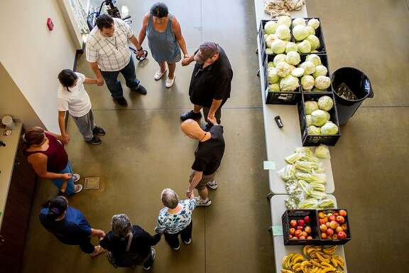 A circle prayer at the San Jose First United Methodist Church on Wednesday, July 25, 2018, in San Jose, Calif. Following the prayer, volunteers and church officials organized food donations and delivered them to families in need.