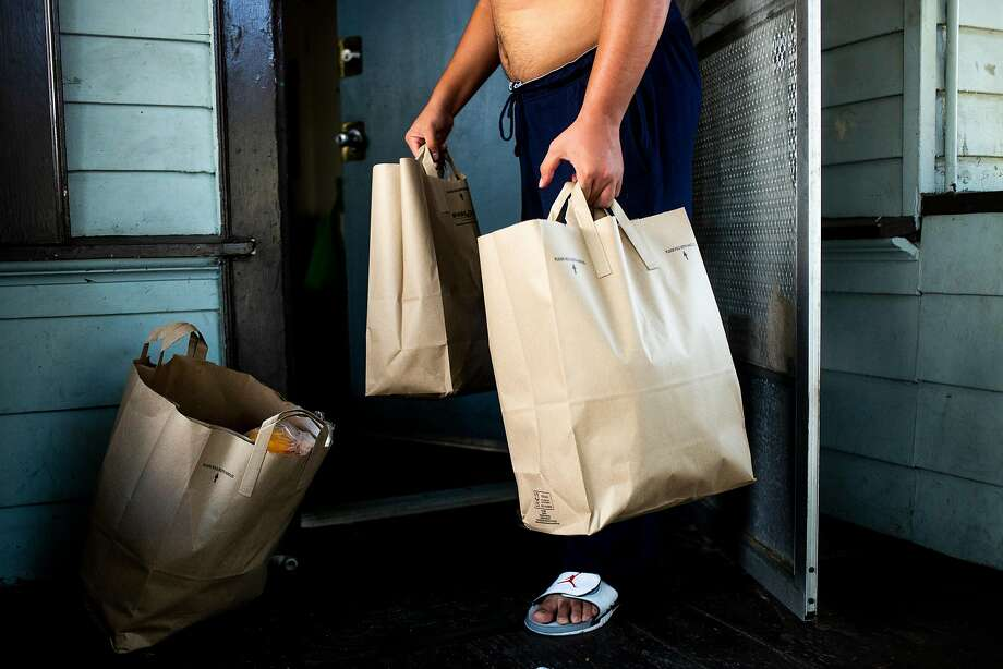 A San Jose man receives bags of donated groceries. Photo: Santiago Mejia / The Chronicle
