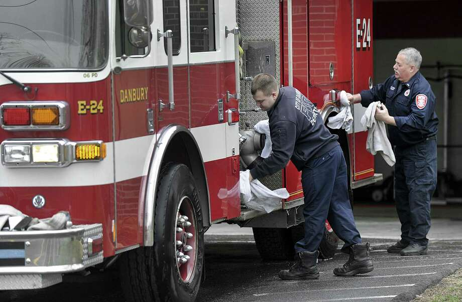 Firefight Eric Freundt, left, and Lt. Tom Corbett, towel dry a firetruck Wednesday morning after it's daily wash at the Engine 24 fire house on Eagle Road in Danbury, April 5, 2017. Photo: Carol Kaliff / Hearst Connecticut Media / The News-Times